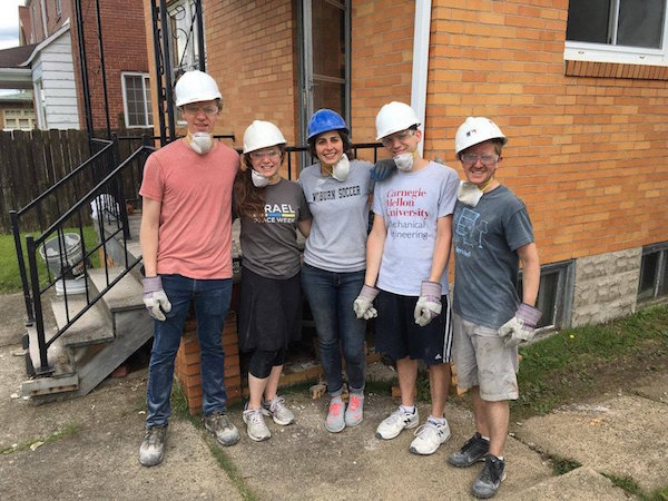 MechE grad students in hard hats pose in front of house at Habitat for Humanity