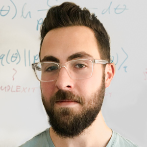 Headshot of Alex Lavin in front of whiteboard with math problems