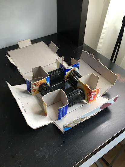 The inside of the cereal box project shows folded cardboard to secure the device inside.