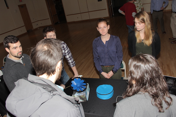 Mechanical engineering students demo a portable hydroelectric device.